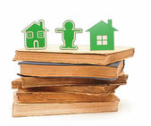 Two small houses made of plastic on a stack of old books — Stock Photo