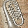 Vintage tuba on cracked brick background — Stock Photo