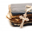 Religion. A cross with a chain against a old book — Stock Photo