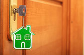 Symbol of the house and stick the key in the keyhole — Stock Photo