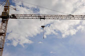 Yellow construction tower crane arm against blue sky — Stock Photo