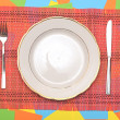 White plate, knife and fork at napkin on colorful background  — Stock Photo