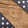 Wooden background with black polka-dot ribbon — Stock Photo #26345869