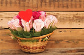 Paper flower in a basket over wooden background. Love concept — Stock Photo