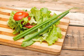Fresh red tomato, green onions, lettuce, parsley, against a wood — Stock Photo
