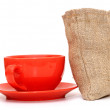 Red cup of coffee with sack of coffee beanson white background — Stock Photo