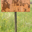 Stock Photo: Weathered plaque on grassy land plot