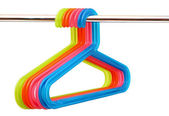 Colorful plastic hangers hanging on a rod over white background — Stock Photo