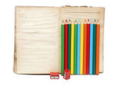 Wooden color pencils and old book on white background — Stock Photo