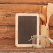 Blank blackboard on wooden surface and wooden utensils — Stock Photo