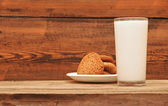 Glass of milk and oat cookies on wooden background — Stock Photo