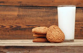 Glass of milk and oat cookies on wooden background, close-up — Stock Photo