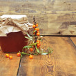 Sea buckthorn berries juice on the glass jar on wooden backgroun — Foto Stock