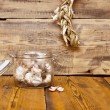 Fresh garlic in glass jar  on old wooden table — Stock Photo