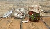 Zon gedroogde tomaten met olijfolie en verse knoflook in glazen pot — Stockfoto