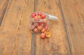 Frisch gepflückten pflaumen in glas auf alten holztisch — Stockfoto