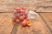 Freshly picked plum in glass jar on old wooden table — Stock fotografie