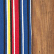 Colorful stripe fabric on wooden background — Stock Photo