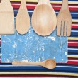 Wooden utensils and old paper sheet on colorful tablecloth — Stock Photo
