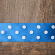 Wooden background with blue polka-dot ribbon — Stock Photo