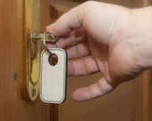 Hand with keys unlocking the front door — Stock Photo