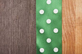 Vintage wooden background with green polka-dot ribbon — Stock Photo