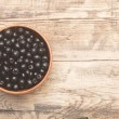 Black chokeberry in brown bowl on wooden table — Stock Photo