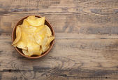 Cheese and chive potato crisp snack in brown bowl on wooden back — Stock Photo
