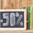 Fifty percent written on blackboard with colorful shopping bag — Stock Photo