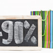 Ninety percent discount written on blackboard with colorful bag — Stock Photo #33309967