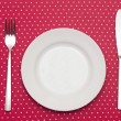 Empty white dinner plate with utensils on fun red polka dot tabl — Stock Photo