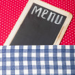 Menu title written with chalk on blackboard lying on tablecloth — Stock Photo