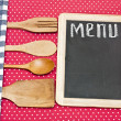 Stock Photo: Menu title written with chalk on blackboard lying on tablecloth