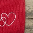 Stock Photo: Two embroidered heart on brown background