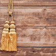Gold rope with tassel against wooden wall — Stockfoto