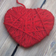 Heart made of red wool yarn on wood background — Stock Photo #33698381