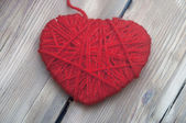 Heart made of red wool yarn on wood background — Stock Photo