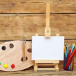 Wooden easel with clean paper and artistic equipment — Stockfoto