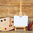 Wooden easel with clean paper and artistic equipment — Stock Photo