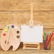 Wooden easel with clean paper and wooden artists palette loaded — ストック写真