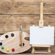 Wooden easel with clean paper and artist color palette — Stock Photo