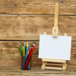 Wooden easel with clean paper and colorful pencils — Stock Photo