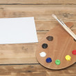 Wooden art palette with paint and brushes and blank white paper — Foto Stock