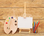 Wooden easel with clean paper and wooden artists palette loaded — 图库照片