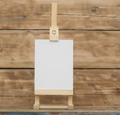 Blank canvas on wooden easel againt wooden background — Stock Photo