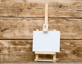 Wooden easel with clean paper on old wooden table — Stock Photo