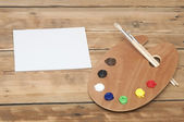 Wooden art palette with paint and brushes and blank white paper — Stock Photo