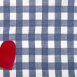 Red heart shape on checkered textile background — Stock Photo #34058387