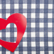 Red heart shape on checkered textile background — Stock Photo