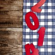 2014 new year on checkered textile background border old wood — Stock Photo
